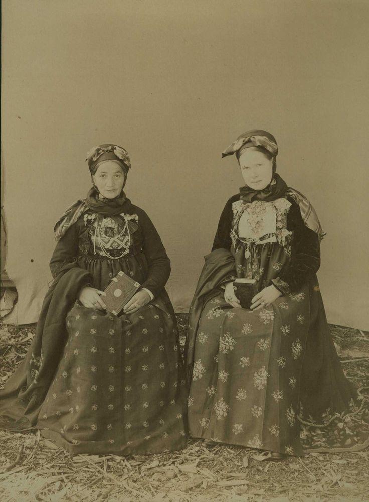 Kvinnedrakter, kone og jente, Nes, Hallingdal, Buskerud.  Kona har tørkleet på høyre, jenta på venstre side. Kvinnene sitter utendørs foran bakteppe med bok i hånda.
