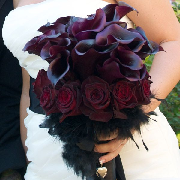 Deep purple calla lilies with dark red roses and black feathers.