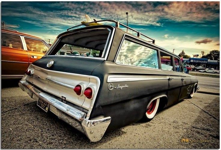 Ratrod Chevrolet Impala wagon complete with a surfboard up on the roof rack, red wheels, and wide white wall tires.