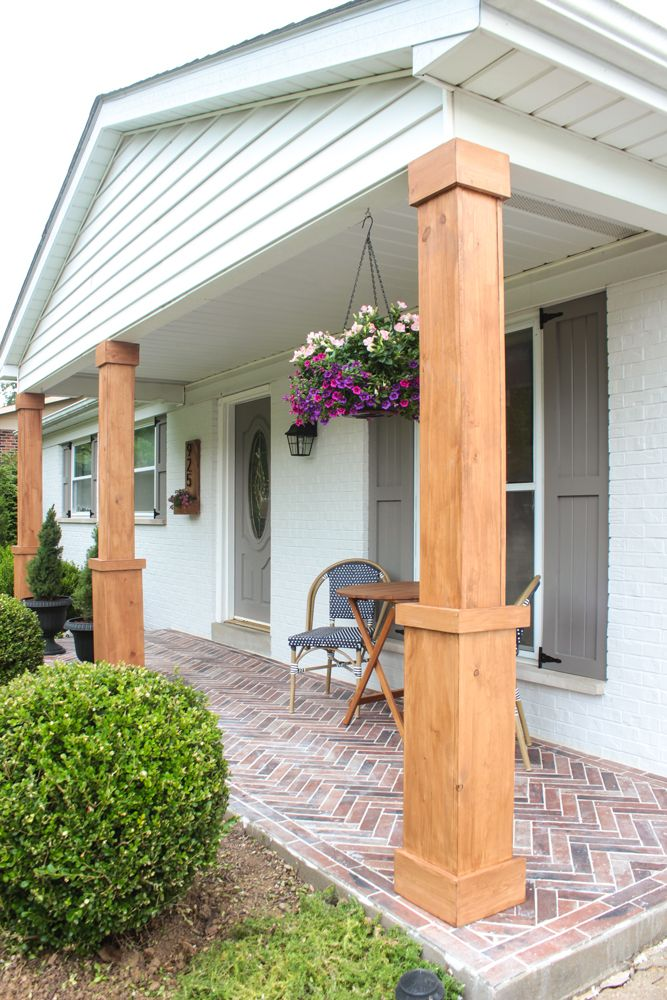 How I made over my small front porch by painting the brick, shutters and front door, wrapping the columns in stained wood, and installing brick tile.