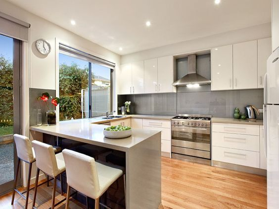 U-shaped with breakfast bar, white gloss cupboards and free standing oven/stove.