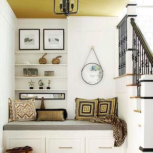 BHG - entrances/foyers - country entryway, coastal entryway, foyer, beadboard walls, white beadboard, painted ceiling, mustard ceiling, wrought iron spindles, geometric pillows, faux fur throw, captains mirror, hanging captains mirror, black and white art, storage bench, built-in storage bench, gray cushion, gray seat cushion, light hardwood floors, wooden stair treads, nautical decor, contemporary lantern pendant, lantern pendant, entryway nook, stairway nook, seating off stairwell