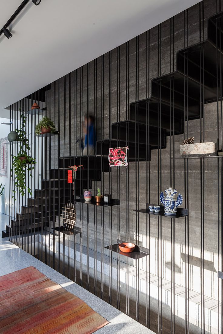 A staircase suspended behind a screen of steel rods and welded shelves features inside this house in Tel Aviv