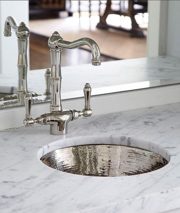 Wet bar boasts a marble countertop fitted with a round hammered metal sink and a vintage faucet under a mirrored backsplash.