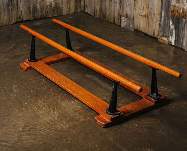 Vintage gymnastics apparatus with wooden bars and cast iron supports.