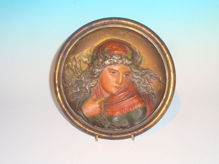 "This very fine 8 1/2"" diam. plaque is marked B 1811 on the reverse. The reverse is painted in a burnt orange and the obverse has an overall paint of subtle greens and reds, facial tones and eyes are natural and her flowing hair is interlaced with what appears to be Holly berries in foliage. A very splendid example with well preserved appearance and surface which gives it the appearance to the eye of it being a cold painted bronze."