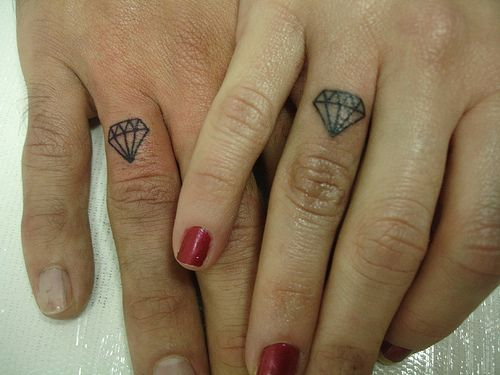 diamond tattoos on the couple's ring fingers.