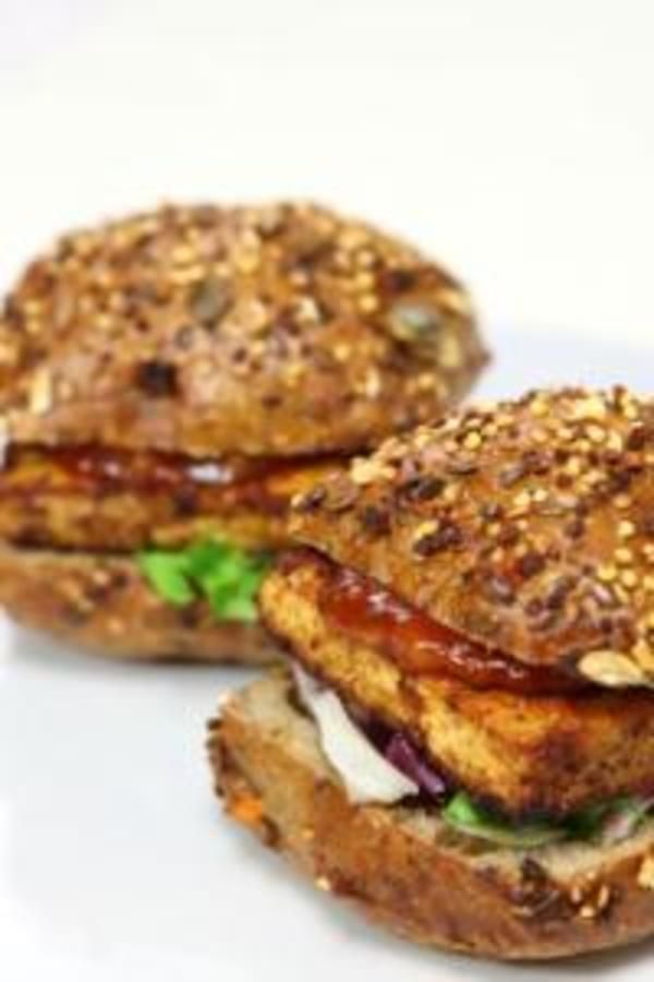 Substitute that meat for marinated tofu for an easy substitute on the grill for these marinated tofu burgers on a seeded bun.