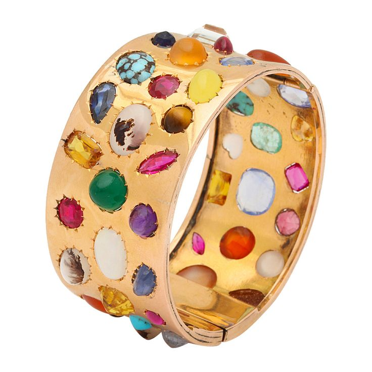 18k gold bangle set with an array of gemstones including ruby, emerald, sapphire, turquoise, opal, garnet, moss agate, goldstone, aquamarine, amethyst, and tiger's eye. American, ca. 1970