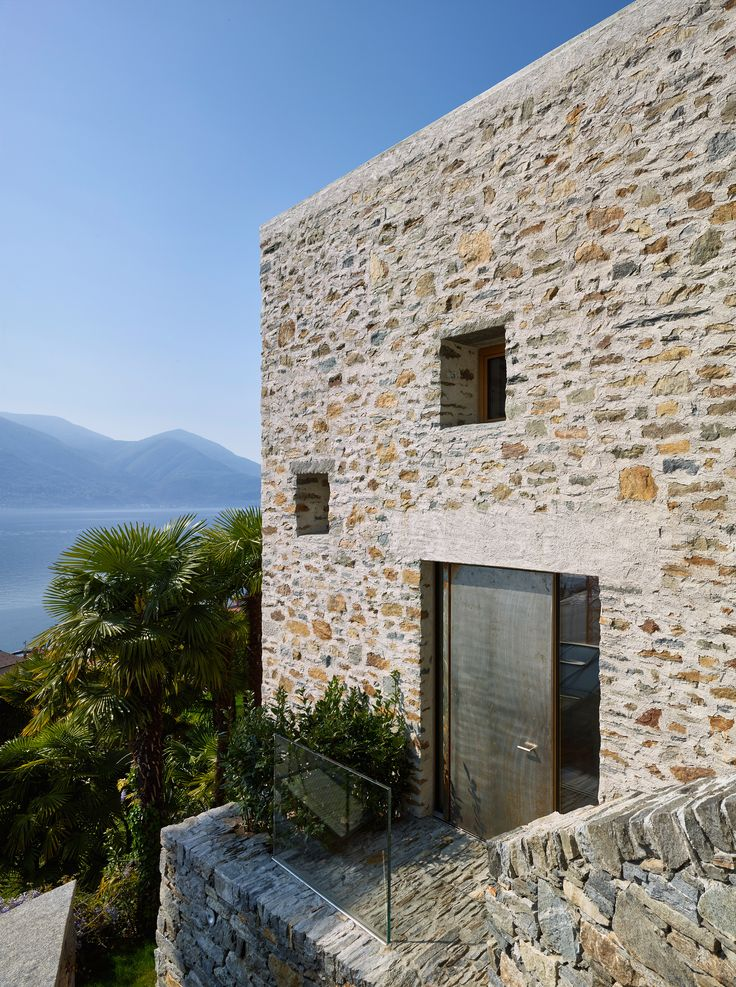 Variously sized openings in the traditional stone and plaster facades of this house provide views of the garden and Lake Maggiore.