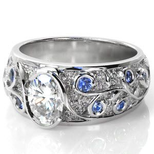 This custom wide band features an oval cut diamond center in a half-bezel wrap setting. The elegant flow of the relief-engraved filigree pattern compliments the center setting. The stippled background highlights the polished luster of the vines, while blue ceylon sapphires sparkle from the curls. #engagement #wedding #ring #jewelry www.knoxjewelers.biz