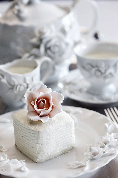 Miniature cakes frosted with buttercream and topped with pink sugar roses are a sweet alternative to a slice of cake.