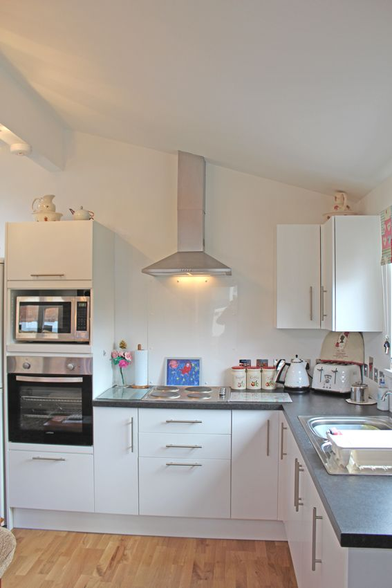 Grannny Annexe white, modern fitted kitchen with chrome extractor hood built by Granny Annexe www.grannyannexe.com