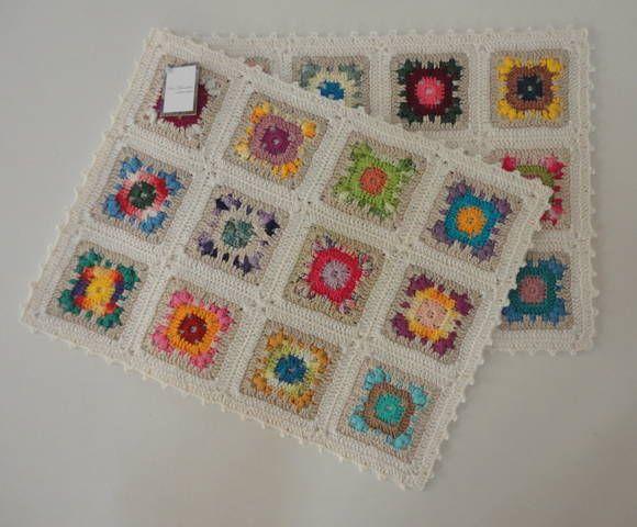 Jogo americano de crochê na cor cru com quadrados multicoloridos; o jogo é composto de duas peças individuais, possui antiderrapante e antitérmico.