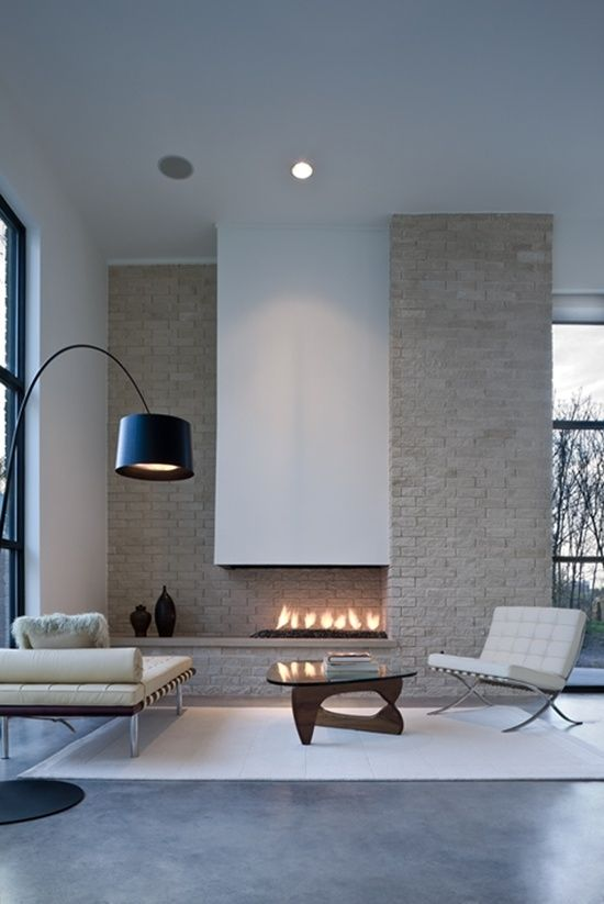 Minimalist living room w/ white leather sofas & modern fire place