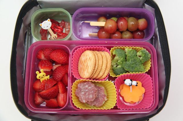 This bento includes fresh diced strawberries with bunny fork, crackers, nitrate-free salami from Trader Joe's cut into flowers, broccoli, organic Applegate cheddar cheese cut into flowers, skewers of grapes, and Annie's bunny fruit snacks.