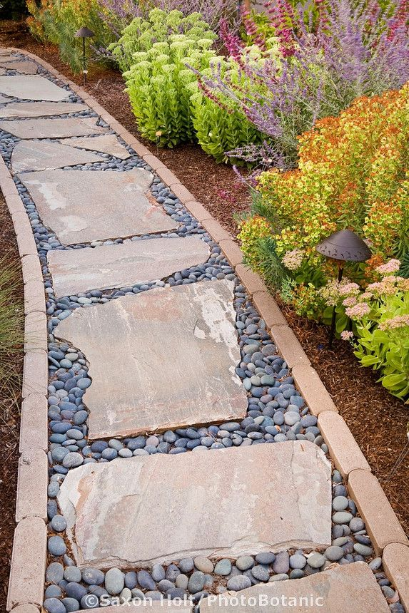 A pathway lined in brick with stepping stones and pebble filler.
