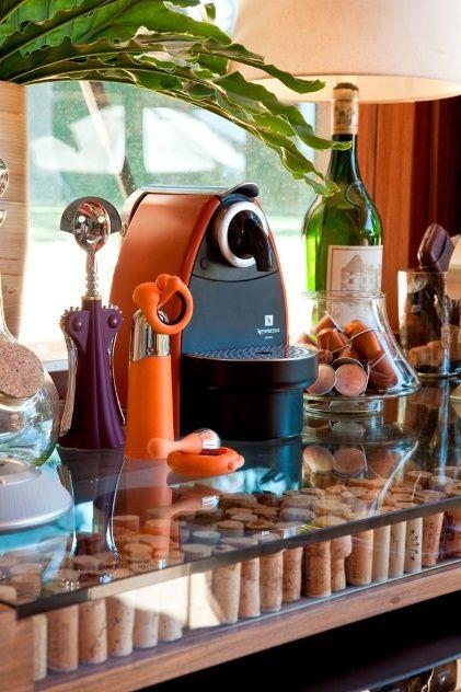 No detalhe do bar, a bancada com tampo de vidro removível foi projetada por Fernando Piva para armazenar a coleção de rolhas. No espaço também há uma cafeteira