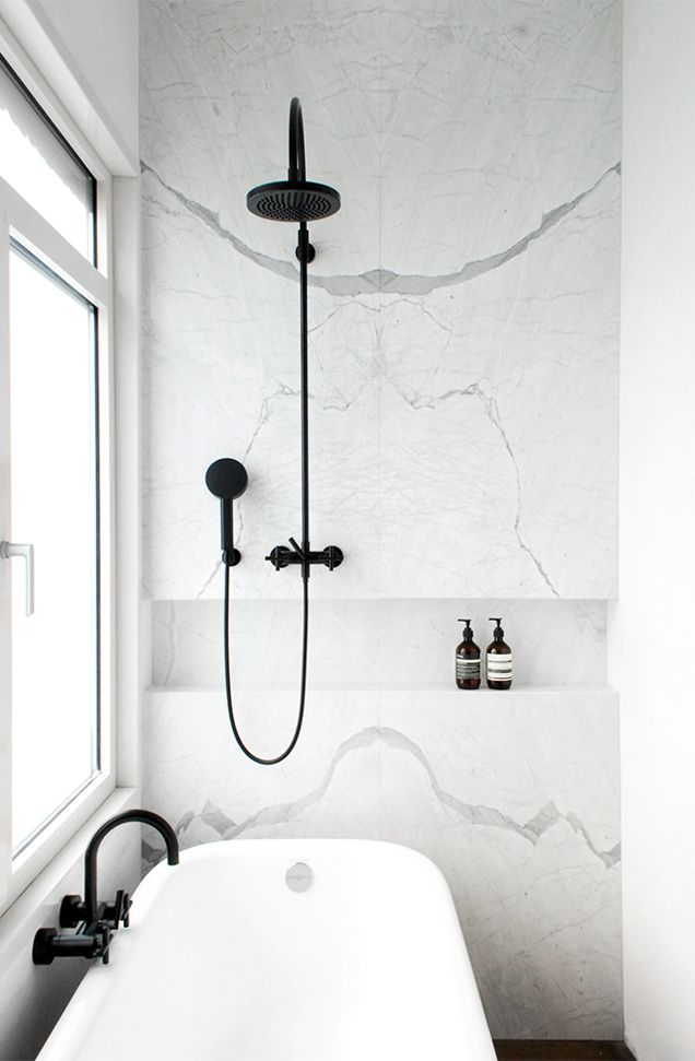 White Statuarietto marble bathroom wall + black shower. (by Dieter Vander Velpen Architect)