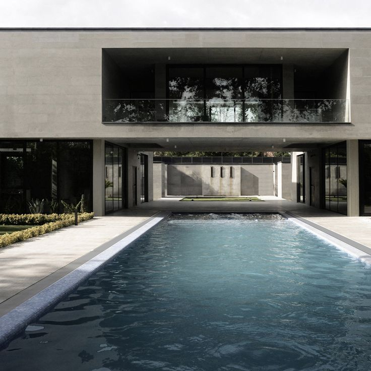 An elevated passageway spans a swimming pool to connect the two monolithic blocks of this weekend home in the Iranian city of Karaj by Kamran Heirati Architects.