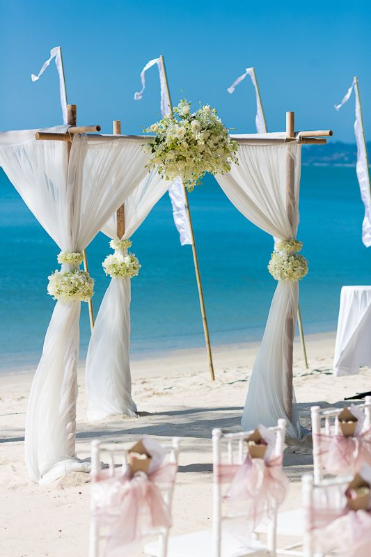 Beach alter. thailand wedding. white silk with orchids and roses, bali flags