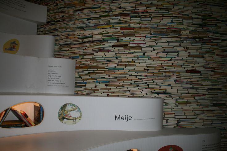 voorbeeld uit kinderboekenmuseum: boekenwand met geïntegreerde leeslampjes, en iets te steriele trap met teksten en spannende gaten