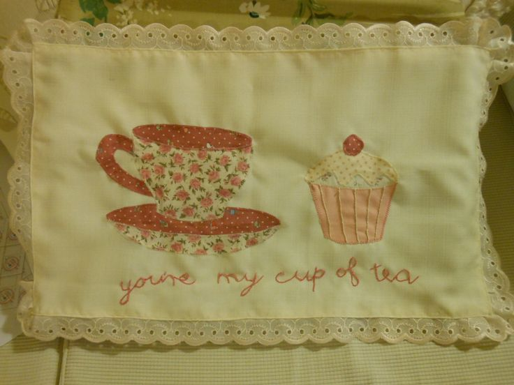 """Traycloth appliqued with a floral teacup and cupcake.  The words """"You're my cup of tea"""" embroidered underneath. Trimmed with lace, ideal for a bone china teaset!"""
