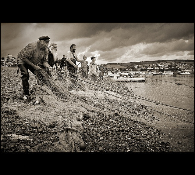 please view large version    We stumbled across this extraordinary fishing ritual on the beach in Shaldon, South Devon this summer (2009).  At low tide a fisherman rows a boat out into the mouth of the estuary, paying out a long line of fishing net (pos http://bamboonets.com/netting-techniques-2/hand-nets/