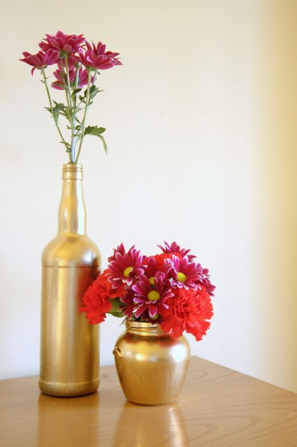 GOLD VASES - I recycled some glass bottles and jars. I then painted with spray gold. I like that coarse finishing due to handmade that gives a vintage and smooth mood. Gold is awesome with a color combination of red and fuchsia but I will try with many other color combinations.
