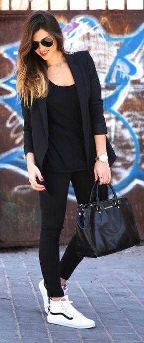 Chica usando un traje en color negro y zapatillas de color blanco