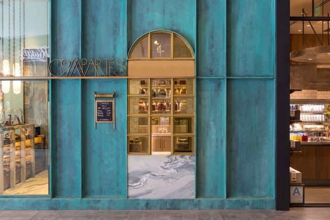 Inside the Compartés Los Angeles store designed by Kelly Wearstler. The space boasts a washed teal exterior, brass framework and details and marble floors.