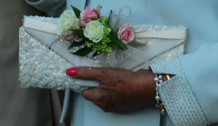 The dilemma for mother's of the bride is always the question of corsage, floral bracelet, bouquet, etc.  This mother of the bride chose to pin her corsage to her purse. Not a new idea. . . but certainly a beautiful one and worthy of consideration!