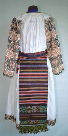 Romanian Women's costume, county of Bistriţa-Năsăud; The underskirt (poale), embroidered above the hem, and vertical rows on the sides. Front and back aprons (catrinţe) of a single width of felted wool. The front apron is maroon w/ 2 black woven stripes with floral embroidery. The back apron has woven stripes in pink, brown, blue  with 2 rows of matching embroidery. Both aprons have green and brown crochet lace on the hem Narrow belt (brâu) woven in red, blue and black stripes.