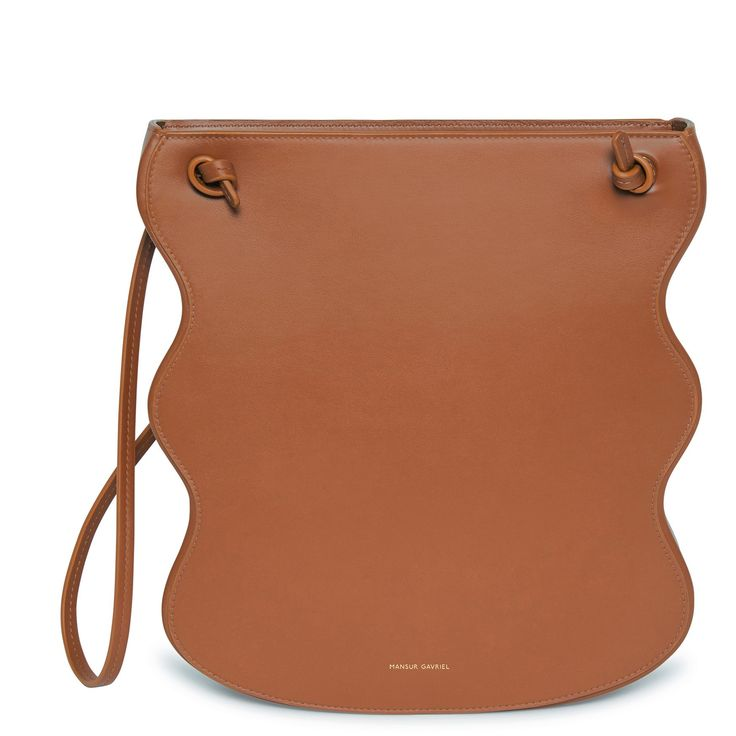 Italian calf leather ocean bag with beige canvas interior and scalloped edge. Shoulder strap and interior side pocket. Made in Italy.