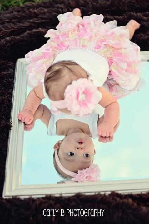 Maybe baby on its side on mirror then one with mom n dad holding mirror with baby's reflection or all their reflections &  baby on it or in front with Sissy's reflection in it