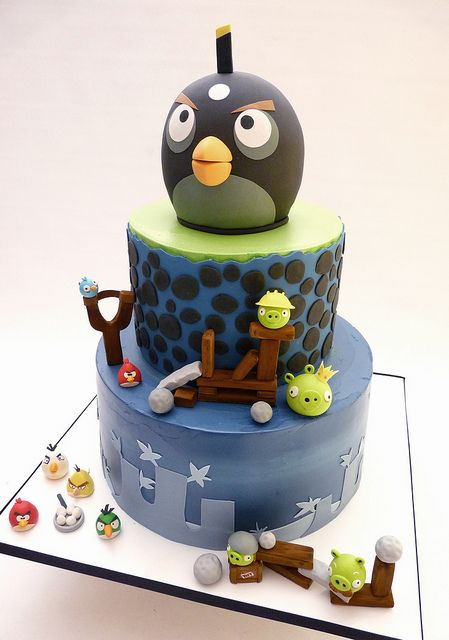 An angry birds Cake  cake iced in buttercream, top tier has a fondant wrap. gumpaste characters. top black bomb bird, made out of krispies and fondant.