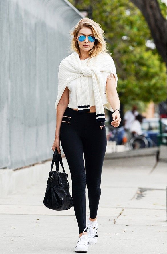 Gigi Hadid wears a white t-shirt, sweater tied over her shoulders, leggings, adidas Superstar sneakers, a black tote, and mirrored aviator sunglasses