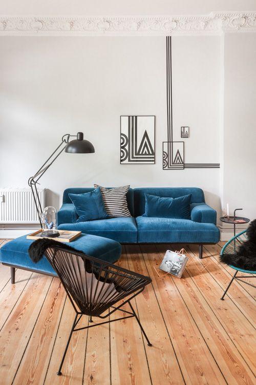 Ce canapé bleu canard et accessoires noirs, c'est chic et tendance. Et j'adore le trompe-l'oeil au mur / les lignes du tableau qui se prolongent sur le mur !
