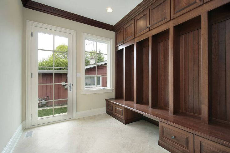 Entryway bench with storage and coat rack. Mudroom ideas and designs with a big hard wooden bench with plenty of storage drawers underneath and above small individual cabins. Cream tile flooring with a small vent.