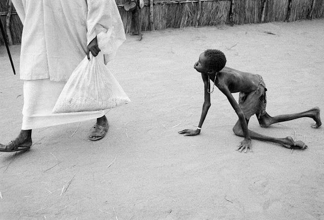 Um homem sudanês bem nutrido rouba milho de uma criança morrendo de fome durante a distribuição de alimentos em um centro de alimentação de ajuda humanitária em Ajiep, no Sudão, em 1998.