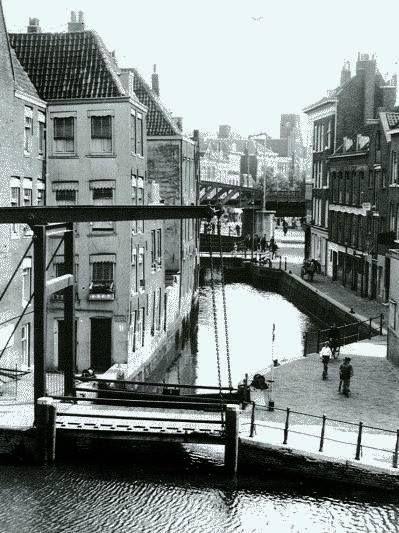 Rotterdam - Zicht op de Stokvisbrug en het Stokvisverlaat vanaf een huis aan het Haagseveer. De kade rechts van het water heette het Stokviswater. Op de voorgrond de Delftsevaart. De brug verderop heette de Oppertbrug, en daarachter was een kolk van de Rotte met een stukje viaduct van het luchtspoor. We zien nog de stomp van de Blauwe Molen die op de hoek stond van de Gedempte Binnenrotte en de Pompenburg. Rechts van de tweede brug iets verderop is de Oppert.