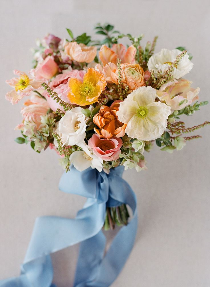 coral, pink and peach  tropical bouquet tied up with blue silk | Photography: Joel Serrato