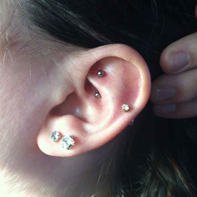 Two lobe piercings at the bottom, a helix piercing on the side, and a rook piercing in middle.