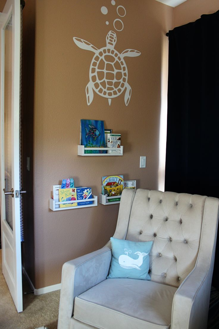 Beach Themed Nursery with Ikea Spice Racks painted white and used as baby book shelves.