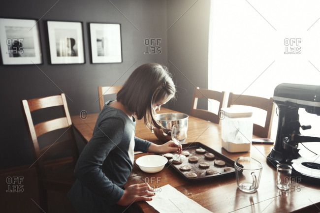 Young girl decorating unbaked cookies on baking tray