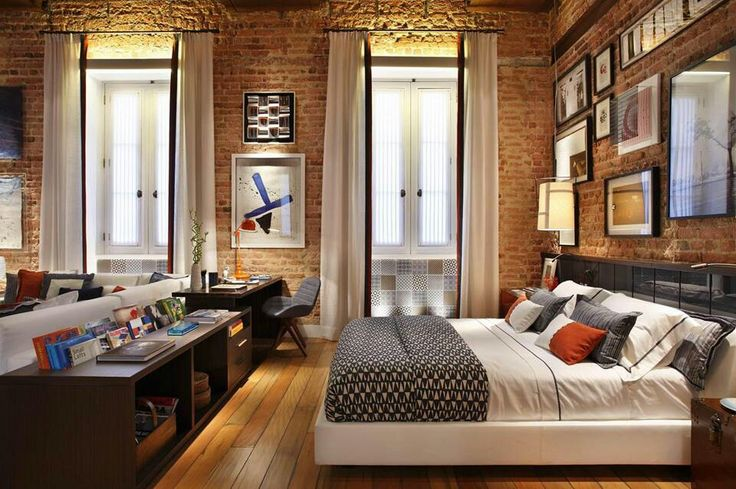 Long curtains against exposed brick in a loft bedroom.