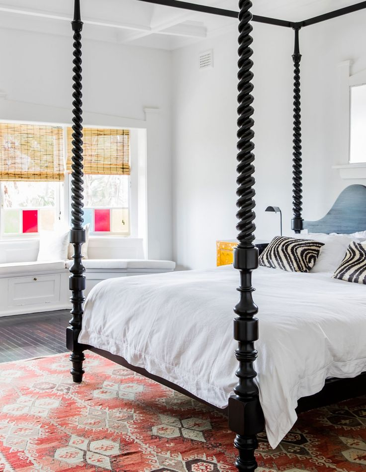 black spool wooden canopy bed + white + bright accents