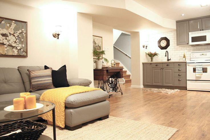 This basement family room was kept bright and cheerful by adding in lots of lighting and incorporating a mostly neutral scheme of warm white walls and grey with a few pops of golden yellow.