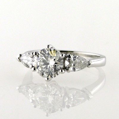 Round brilliant cut diamond with pear cut diamonds on the sides