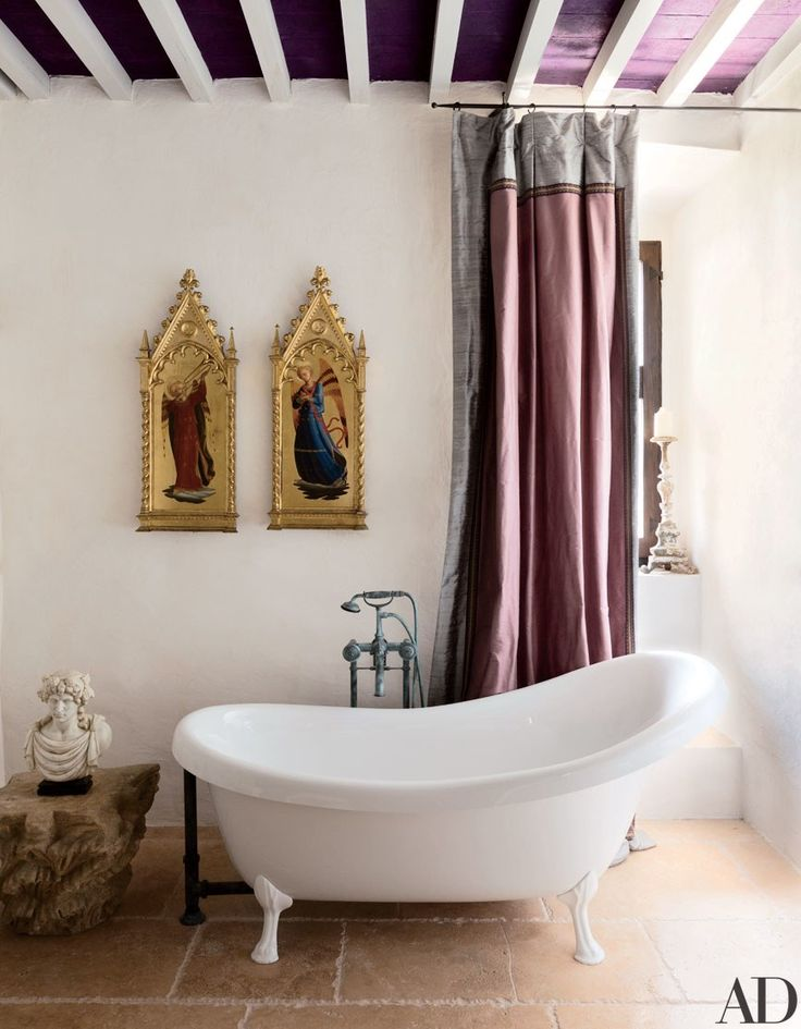 A claw-foot tub and decadent drapery are fitting for this washroom inside a remodeled castle in Umbria, Italy, a project of architect Domenico Minchilli and decorator Martyn Lawrence Bullard. The use of religious imagery and ancient sculpture makes for a very royal bathing experience. The purple ceiling boards bring unexpected color to the sun-drenched room.